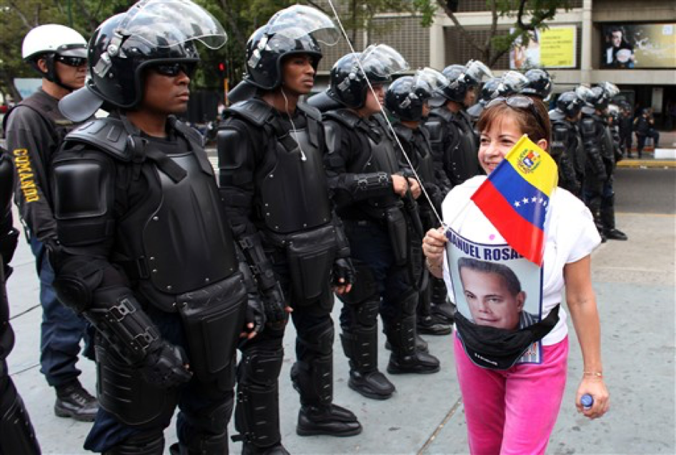 Spot the social movement: an anti-Chávez civilian protestor walks by the armed police of Chávez's state.
